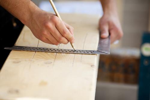 zimmermann zeichnet auf holzbalken